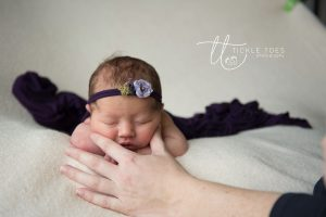 picture newborn baby with head on hands. mum holding head for safety